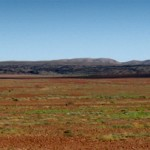 One of the few interruptions to the flat landscape along the Oodnadatt a Track, a range of hills in the distance provides some welcome relief .